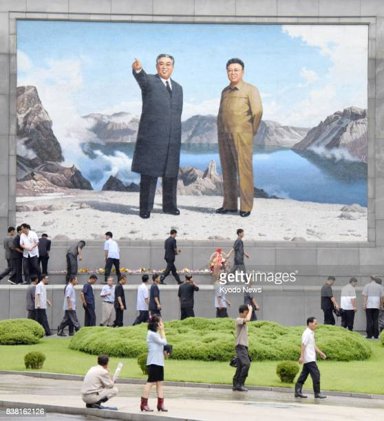 People offer flowers in front of a large mosaic portrait of Kim Il Sung founding father of North Korea and Kim Jong Il his son and father of current...