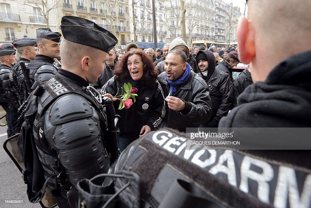 People offer flowers to gendarmes during a protest gathering about 150 employees of French auto giant PSA Peugeot Citroen Aulnay outside France's MEDEF employers' association headquarters on March 28, 2013 in Paris, to protest against the planned closure of their plant.