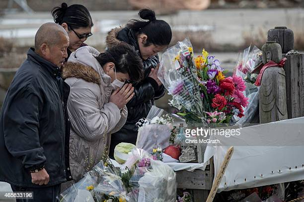 People offer prayers at the memorial site of the Minamisanriku Disaster Emergency Center on March 11 2015 in Minamisanriku Japan On March 11 Japan...