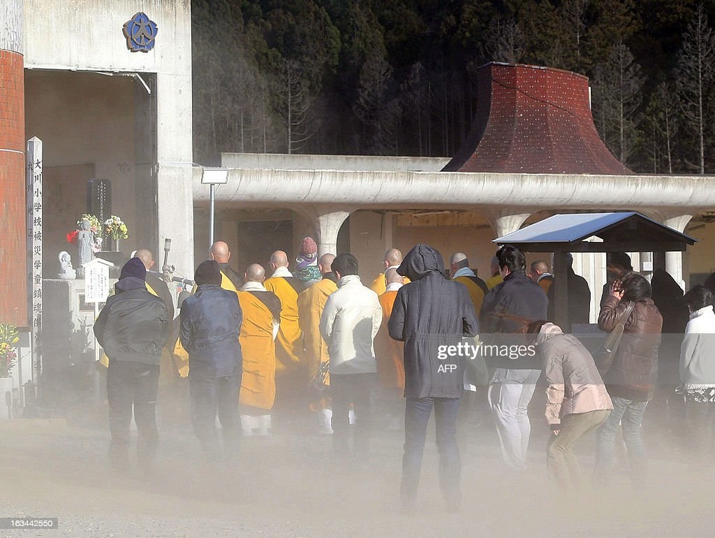 People offer prayers for the victims of March 11 earthquake and tsunami disaster during a strong wind and sand storm at the Okawa elementary school in Ishinomaki, in Miyagi prefecture, northern Japan on March 10, 2013. A huge dust storm hit Japan, blanketing the city with brown dust that blinded many residents and slightly darkened the city, as the cold front quickly moved south. AFP PHOTO / JIJI PRES JAPAN OUT