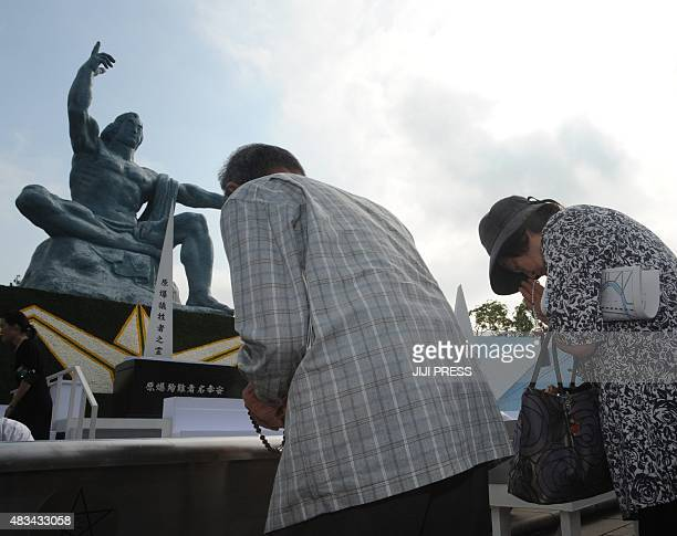 People offer prayers for victims of the World War II atomic bombing at the Peace Statue in Nagasaki on August 9 2015 Japan on August 9 marks the 70th...