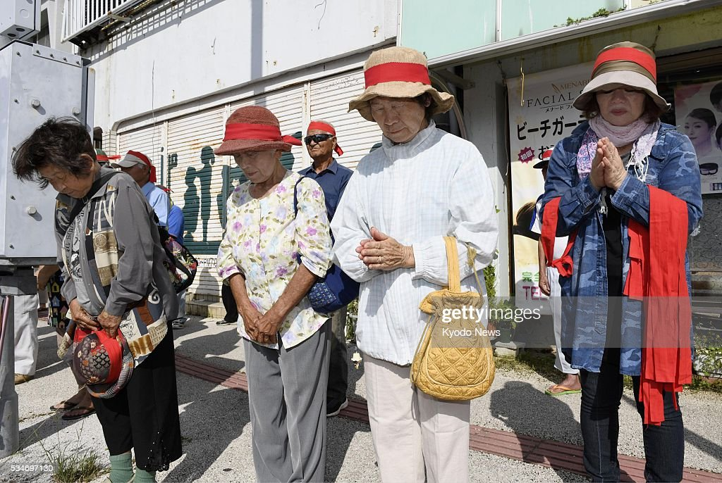 People offer prayers in Uruma, Okinawa Prefecture for a women who a former U.S. Marine has admitted to killing, before participating in a kick-off rally as campaigning for a prefectural assembly election began on May 27, 2016.