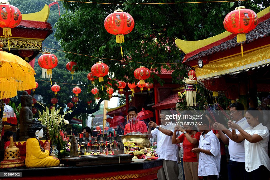 People offer prayers on the first day of the Lunar New Year of the Monkey at the Dharmayana temple in Kuta, near Denpasar on Indonesia's Bali island on February 8, 2016. The Lunar New Year is celebrated in many parts of the predominantly Muslim country of 250 million people where Chinese heritage took roots through ancient transmigration. AFP PHOTO/SONNY TUMBELAKA / AFP / SONNY TUMBELAKA