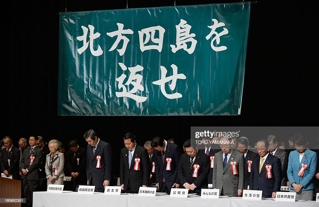 People offer silent prayers during a national meeting to demand the return of what Japan calls the Northern Territories, seized by Russia in the closing days of WWII and called the Kurils in Tokyo on February 7, 2013. Some 2,000 people inclucing former residents of the Northern Territories attended the meeting. Japanese letters in a green banner read 'Get Back the Four Northern Islands.' AFP PHOTO/Toru YAMANAKA