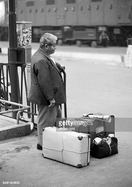 people older man stands on a platform railroad station suitcases luggage aged 60 to 70 years Italy Lombardy Milan