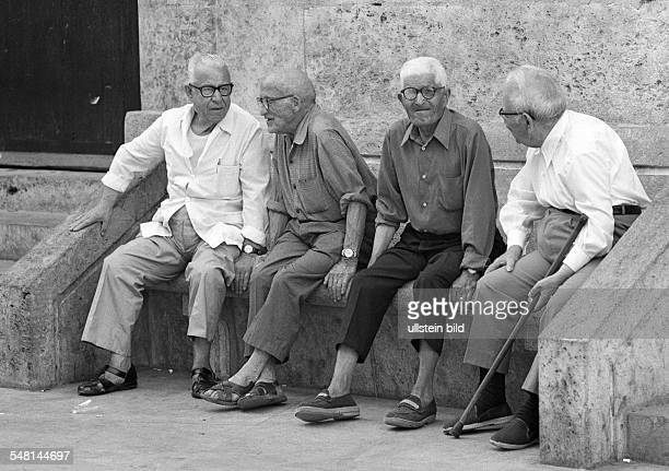 people older people four older men sit on a bench gossip walking stick aged 70 to 80 years Spain Valencia