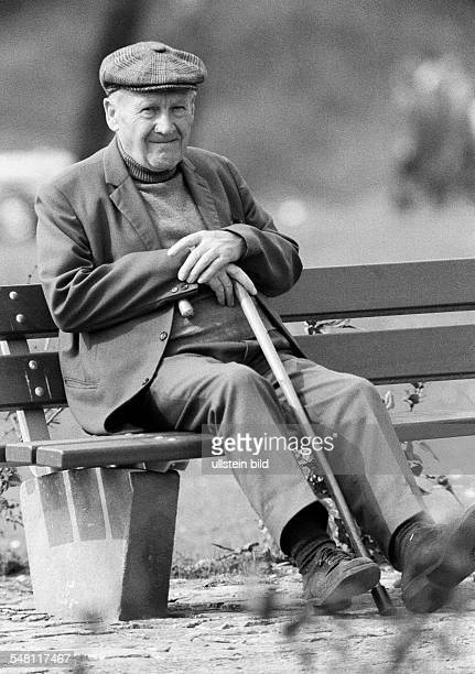 people older people older man with a walking stick sits on a bench aged 70 to 80 years