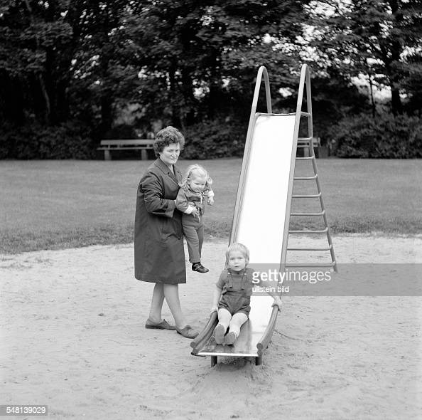 people older woman and two grandchildren on the playground slide aged 50 to 60 years aged 3 to 4 years