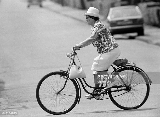 people older woman drives a bicycle aged 50 to 60 years