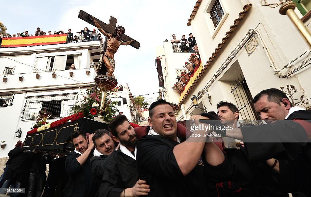 People on a balcony watch as an effigy of Jesus Christ on the cross is carried past during the 'Cristo de la Fe ', populary known as the gypsy Christ parade, Holy Week procession on April 1, 2015 in Alicante. Christian believers around the world mark the Holy Week of Easter in celebration of the crucifixion and resurrection of Jesus Christ.