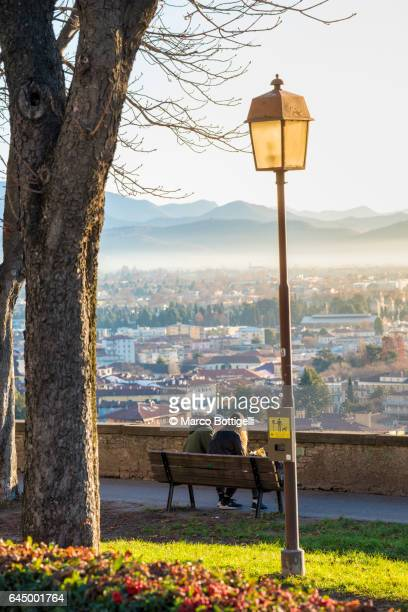 People on a bench in Città Alta (Upper town). Bergamo, Italy.