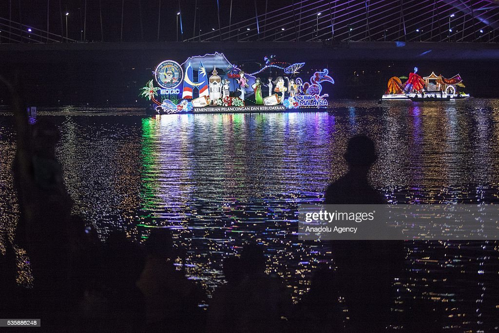 People on a boat watch the colorful decorated boats representing the states of Malaysia during the Magic Of The Night event at Royal Floria flower festival in Putrajaya, Malaysia on May 30, 2016.