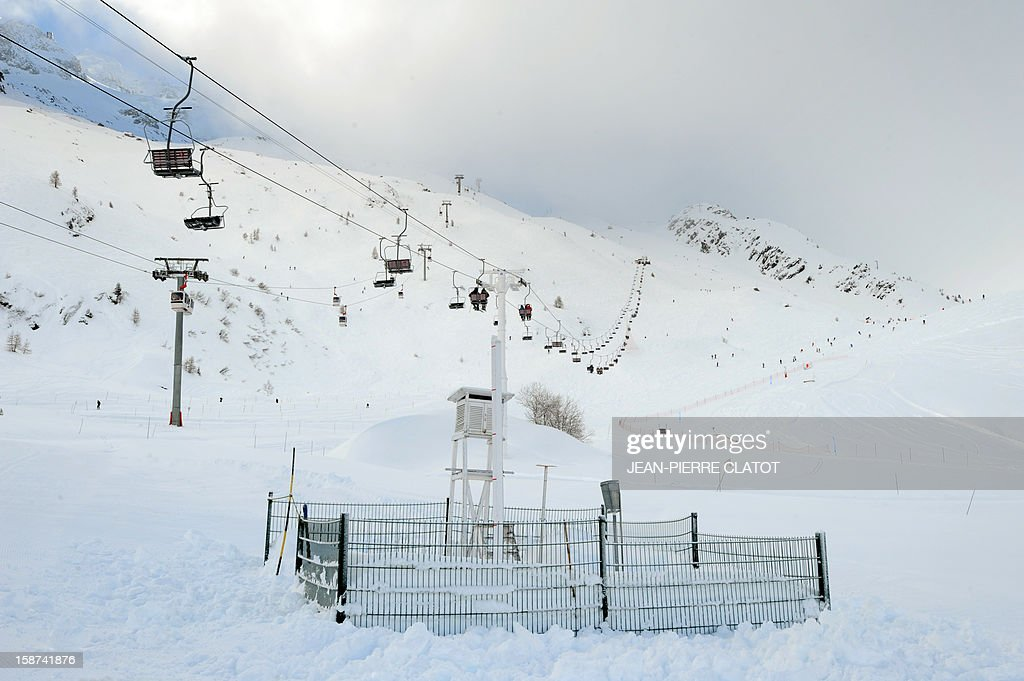 People on a chair-lift pass above an altitude weather station on the Grand Montets' pistes in Argentieres near Chamonix, French Alps, on December 26, 2012. AFP PHOTO / JEAN-PIERRE CLATOT