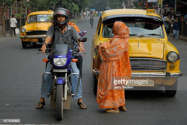People on a motorcycle stopped at a red light ignore the pleas of a Muslim woman begging in the street near the Esplanade