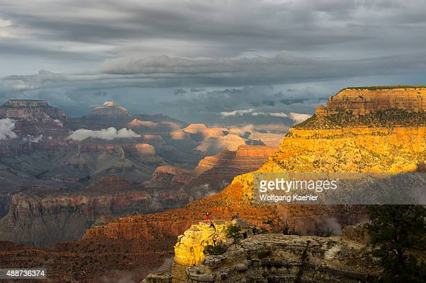 People on a rock outcrop between Yavapai Point and Mather Point on the South Rim of the Grand Canyon with clearing clouds after a thunderstorm in the...