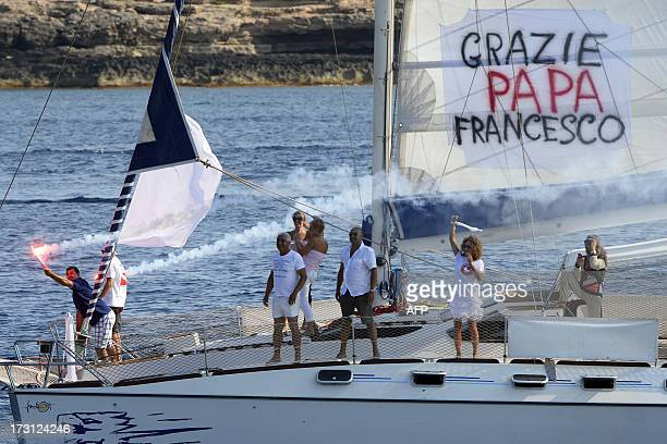 People on a sailing boat with a banner reading 'Thank you Pope Francis' burn flares and wave as the pontiff leaves on a boat to cast a wreath into...