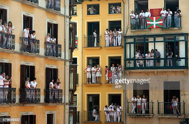 People on balconies witness the 'Chupinazo' celebration that marks the kickoff at noon sharp of the San Fermin Festival in front of the Town Hall of...
