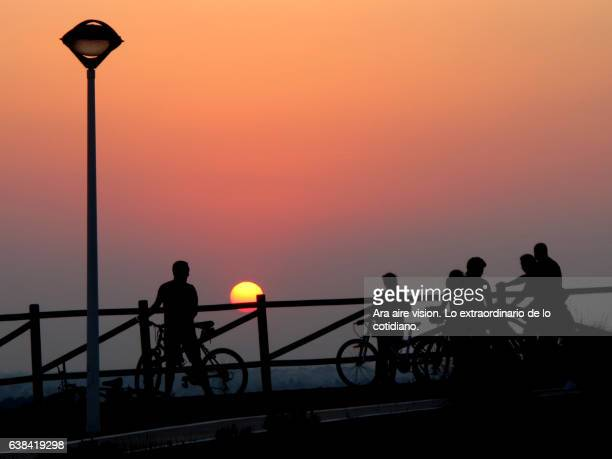 People on bicycle at sunset