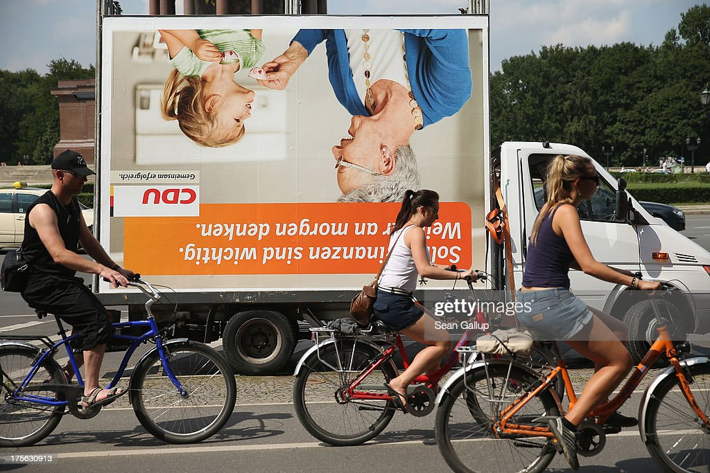 People on bicycles ride past an election campaign poster of the German Christian Democrats (CDU) that is lying on a truck on August 6, 2013 in Berlin, Germany. Germany is scheduled to hold federal elections on September 22 and so far current Chancellor Angela Merkel and her party, the German Christian Democrats (CDU), have a strong lead over the opposition.