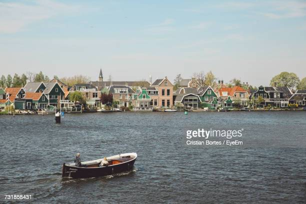 People On Boat In River By Houses Against Sky