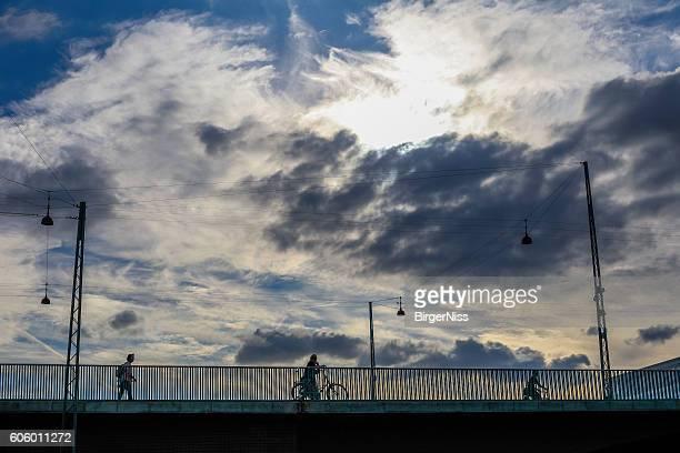People on bridge against dramtic sky, Copenhagen, Denmark