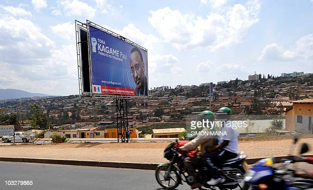 People on motorcycles ride past a poster for Rwandan President Paul Kagame on Timichanga road in Kigali on August 7 2010 ahead of Rwanda's...