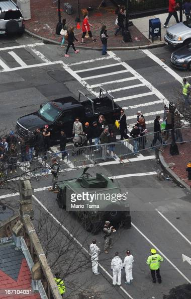 People on Newbury Street watch and walk past crime scene investigators Boston police officers and military personnel at a still cordoned off section...