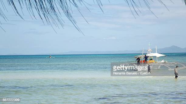 People On Outrigger Boat Moored In Sea