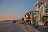 People on paths near beach and ocean at dusk.