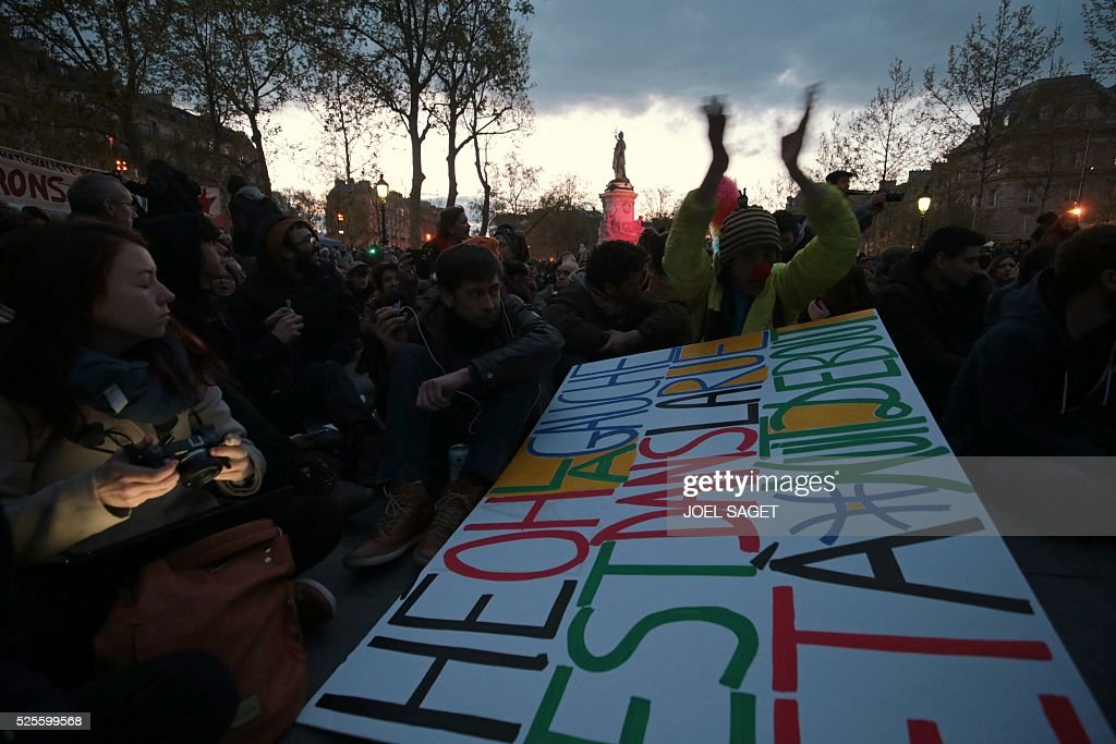 People on Place de la Republique attend the Nuit Debout, or 'Up All Night' movement on April 28, 2016 in Paris. The 'Nuit Debout' demonstrations began on March 31 in opposition to the government's proposed labour reforms. Banners read 'We occupy better than this' and 'Where are you Democracy. Placard reads 'He Oh the Left, we are on the streets and we attend Nuit Debout'.