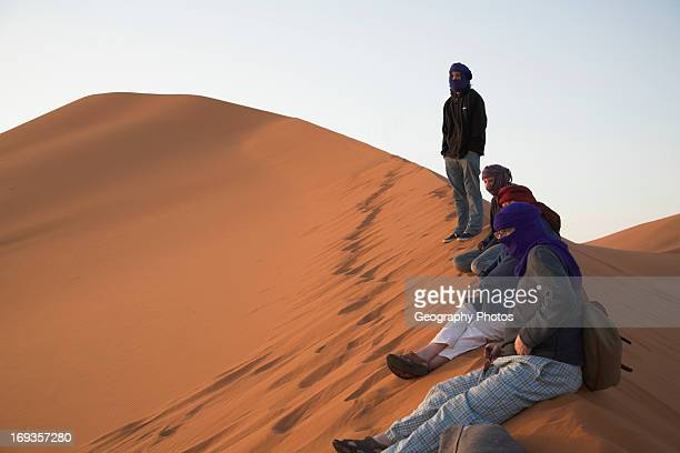 People on ridge of sand dune watching the sune rise Merzouga Morocco