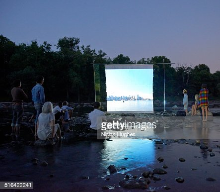 People on river watching movie screen