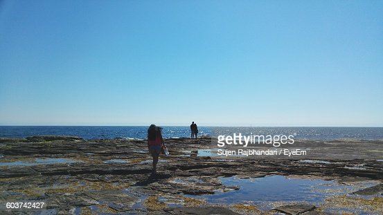 People On Rocky Field At Sea Against Sky