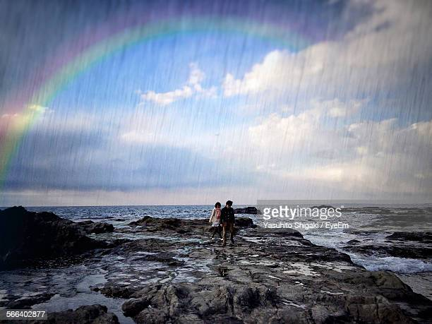 People On Rocky Shore Against Rainbow In Sky During Monsoon