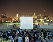 People on rooftop at night, sitting in front of projection screen