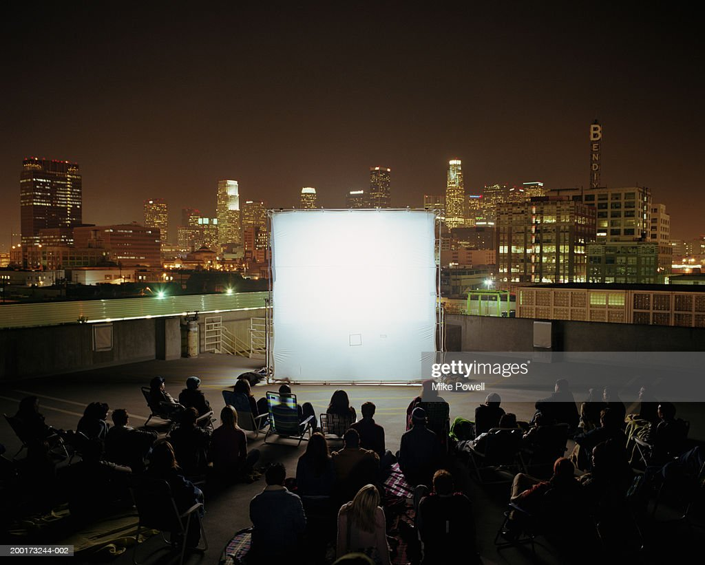 People on rooftop at night, sitting in front of projection screen : Stock Photo
