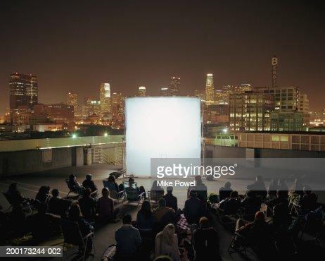 People on rooftop at night, sitting in front of projection screen : Stockfoto