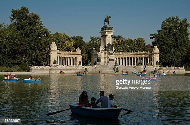 People on rowboats at Retiro Park pond with Alfonso the Twelfth of Spain monument in the background on August 26 2013 in Madrid Spain This pond is...