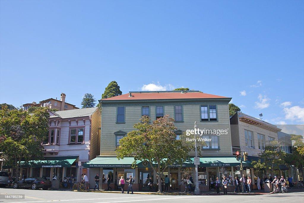 People on sidewalk & street at quaint intersection
