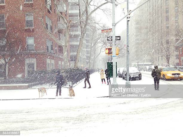 People On Snowcapped Street During Snowfall In City