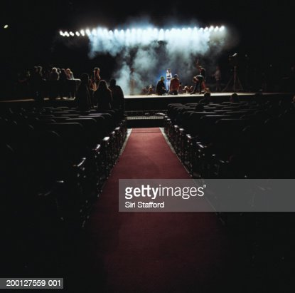 People on stage in empty theater, preparing for event