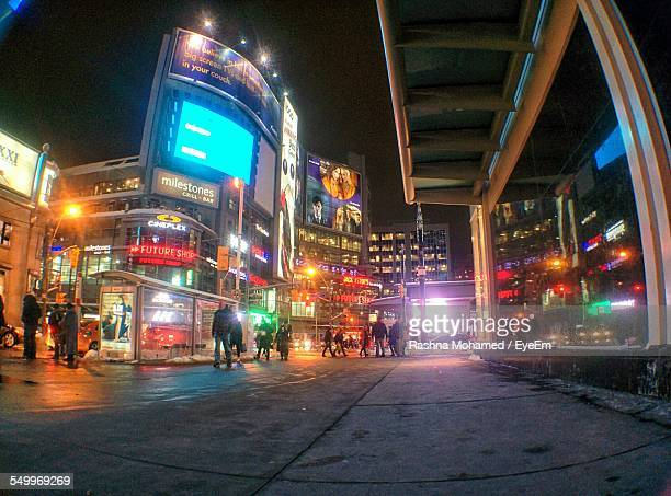 People On Street By City Buildings At Night
