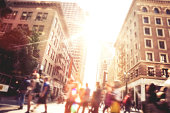 People walking across a street.  The street runs between some tall buildings with even taller buildings in the background.  The sun is shining at the end of the street, casting bright light on the peo