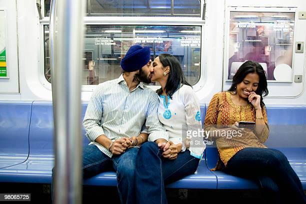 People on subway, messaging on phone, flirting