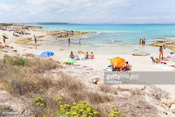 People on the beach in the paradise island of Formentera with turquoise water in summer time Baleàric Islands