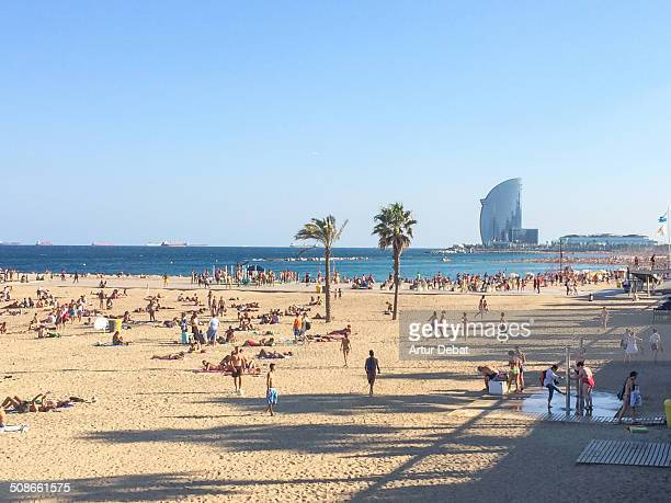 People on the beach of Barceloneta in Barcelona's city in the showers with the Hotel W on the background