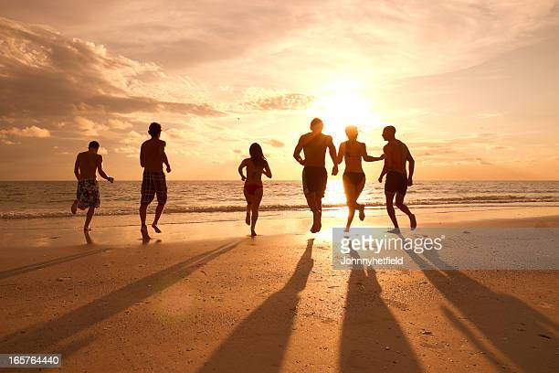 People on the beach running to the water at sunset