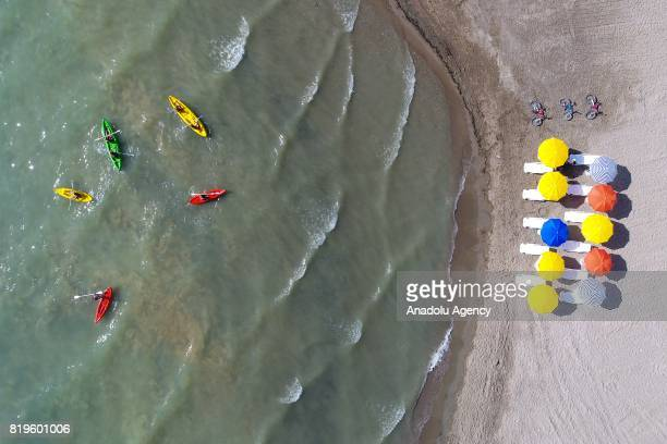People on the boats are seen near the beach of the Van Lake as people swim on a summer day in Edremit District of Van Province Turkey on July 20 2017