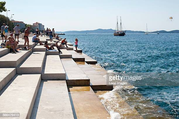 People on the steps of the Sea Organ in Zadar on the Adriatic coast of Croatia