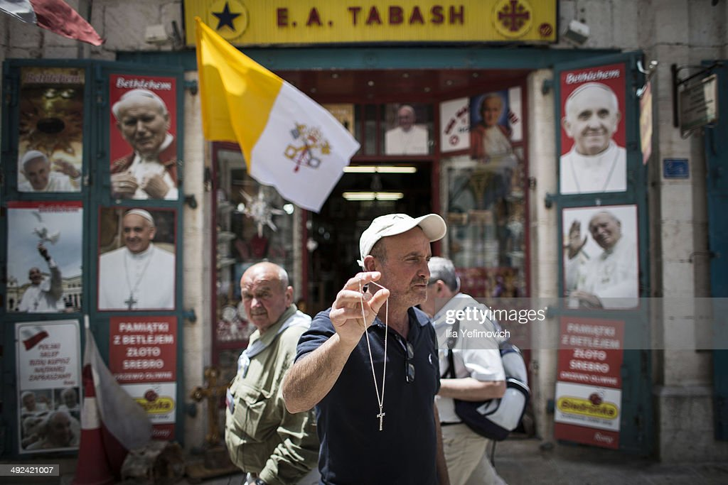 People on the street of Bethlehem pass by posters of Pope Francis on May 20, 2014 in Bethlehem, West Bank. Pope Francis is due to make his first visit to the Holy Land as pontiff and will visit both the West Bank and Israel this coming Sunday. The Pope will celebrate two public Masses during his visit, one in Amman, Jordan and the other in Manger Square in Bethlehem.